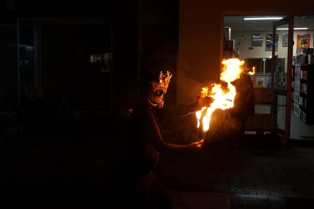 fire performer with fire fingers and skull costume