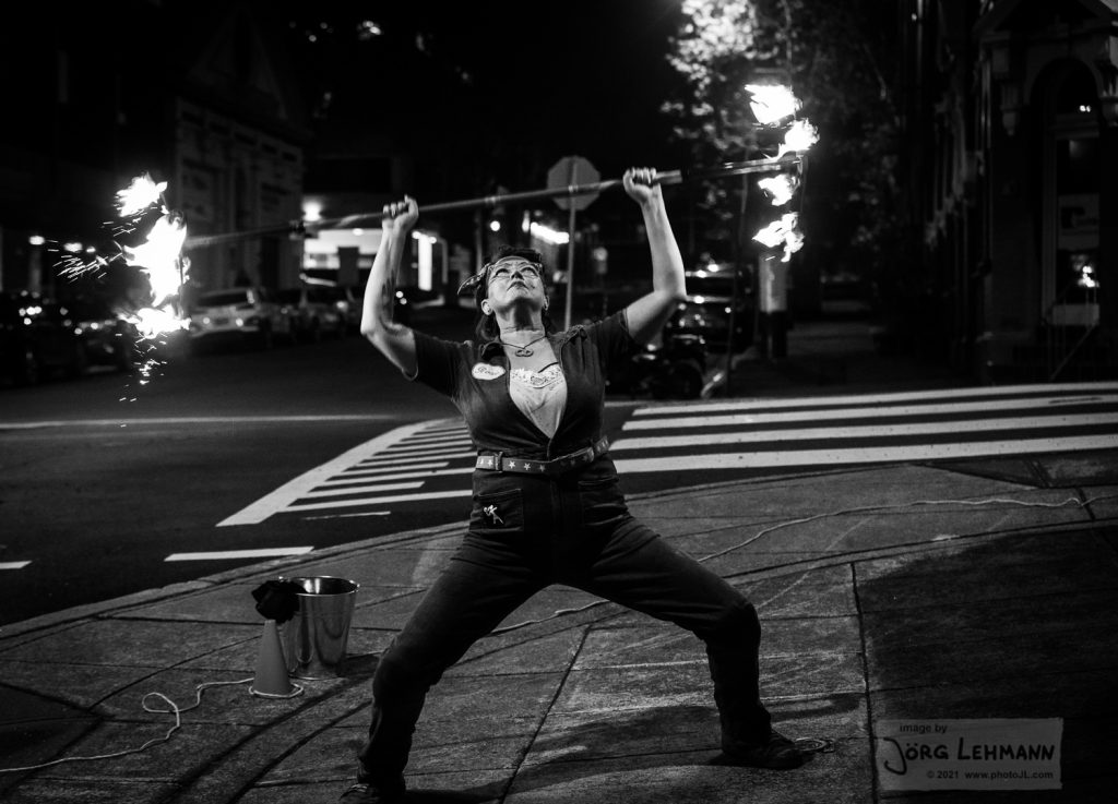 Rosie the riveter costume is a denim boiler suit- this image is in black and white shes pretending to dead lift the staff like a weightlifter. photos by jorg lehmann